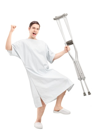 crutch: Full length portrait of a happy male patient in hospital gown holding crutches and gesturing happiness isolated against white background