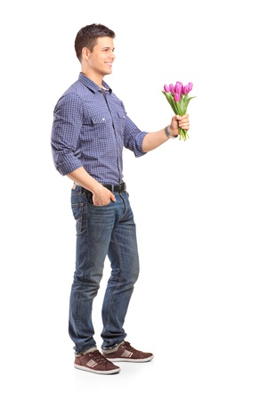 Full length portrait of a smiling guy holding flowers isolated on white background photo