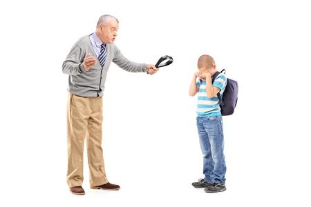 niño llorando: Retrato de cuerpo entero de un abuelo enfadado sosteniendo un cinturón y amenazando a su sobrino aislado en fondo blanco Foto de archivo