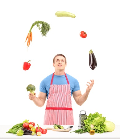 Male with apron juggling with vegetables while preparing food isolated on white background photo