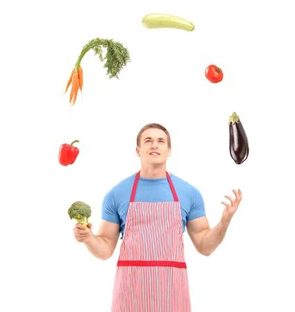 Young handsome male wearing apron and juggling with vegetables isolated on white background Stock Photo