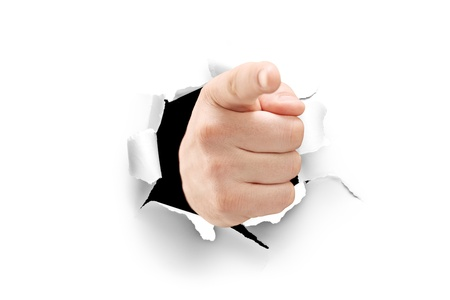 A view of a male hand pointing through a hole in paper isolated on white background photo