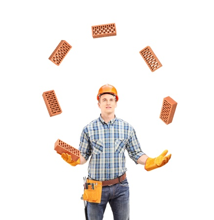 Construction worker juggling with bricks, isolated on white background photo