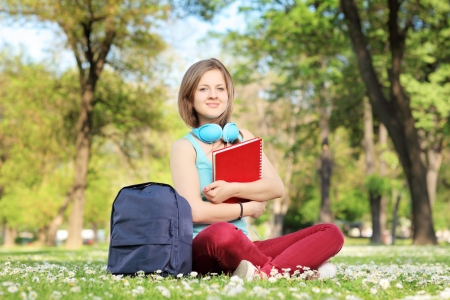 A beautiful female student with book and headphones sitting on a grass in a park photo