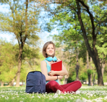 A beautiful young female student with book and headphones sitting on a grass in a park Stock Photo - 19381064