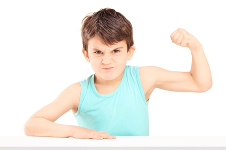 muscle boy: A mad child showing his muscles seated on a table isolated on white background Stock Photo