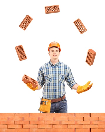 Construction worker juggling with bricks behind a brick wall, isolated on white background photo