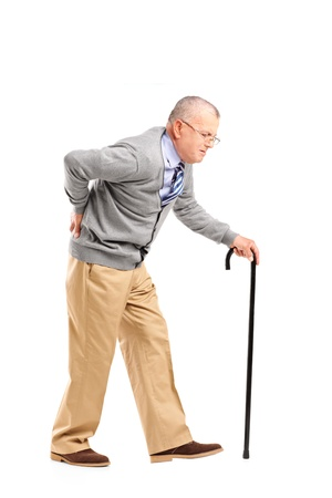 senior pain: Full length portrait of a senior gentleman walking with cane and suffering from back pain isolated on white background