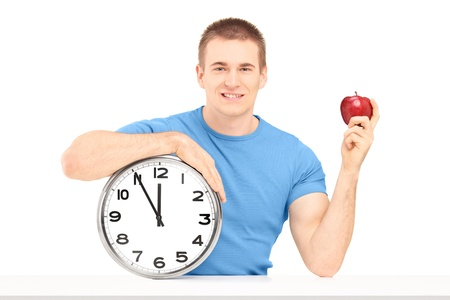 time table: A smiling guy holding a wall clock and red apple on a table isolated on white background