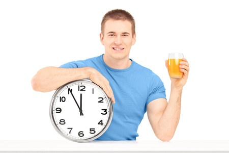 Handsome guy holding a wall clock and glass of orange juice on a table isolated on white background photo