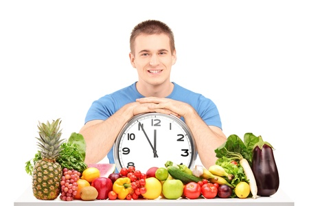 Handsome guy holding a wall clock, seated on a table full of fruits and vegetables, isolated on white background photo
