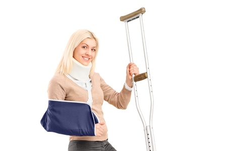 injured woman: A happy blond female with broken arm holding a crutch isolated on white background