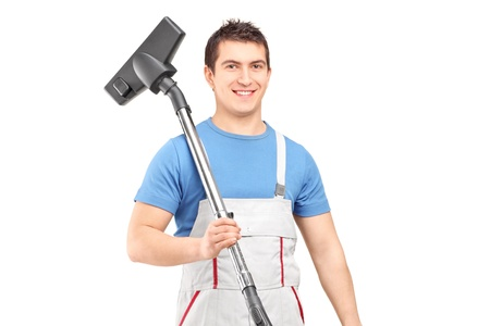 household chores: A young male worker holding a vacuum cleaner isolated on white background