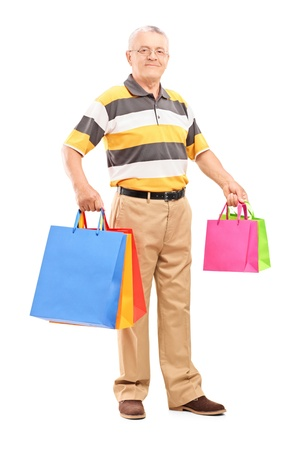 Full length portrait of a mature gentleman with shopping bags isolated against white background photo