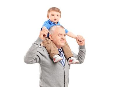 grandchildren: Senior giving a piggy back ride to his grandson isolated on white background