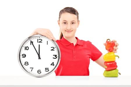 punctual: Una niña sonriente sosteniendo un reloj de pared y los pimientos en una mesa aislada en el fondo blanco Foto de archivo