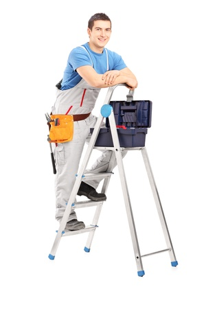 Full length portrait of a handy man posing on a ladder, isolated on white background Stock Photo