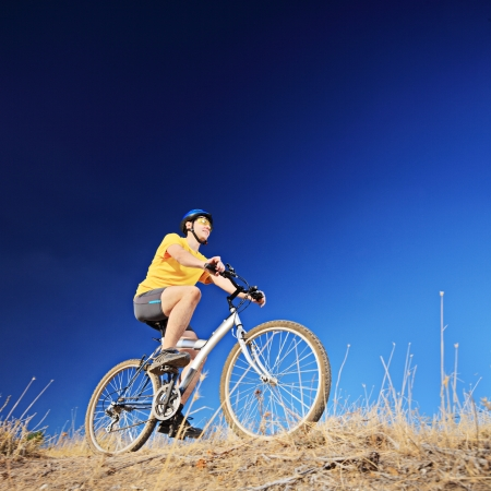 A guy with yellow shirt and helmet riding a mountain bike outdoors Stock Photo - 19406300