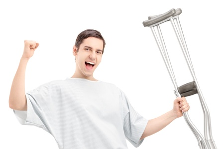 hospital gown: A happy male patient in hospital gown holding crutches and gesturing happiness isolated against white background Stock Photo