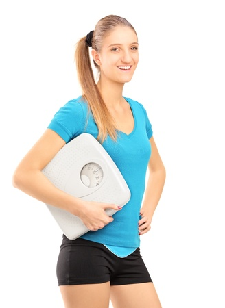 A smiling female athlete holding a weight scale and looking at camera isolated on white background photo