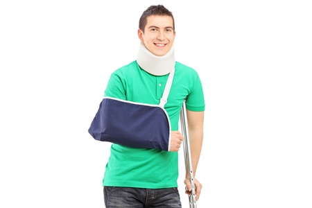 broken arm: Full length portrait of a smiling male with broken arm and crutch isolated on white background