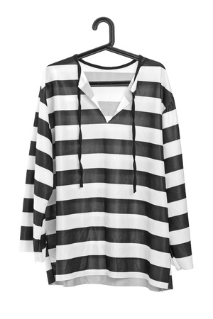 A studio shot of a black and white striped prison uniform on a hanger isolated against white background photo