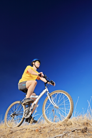 A young male wearing yellow shirt and helmet on a mountain bike Stock Photo - 19406285