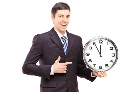 hour hand: A young man in suit pointing on a clock, isolated on white background Stock Photo