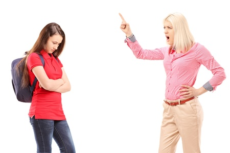 trouble: Angry mother shouting at her daughter isolated on white background