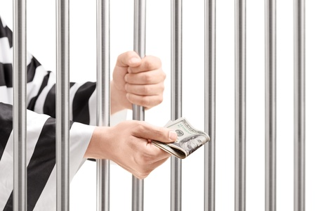Man in jail holding prison bars and giving bribe isolated on white background photo