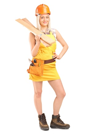 Full length portrait of a smiling female carpenter with helmet holding sills isolated on white background photo