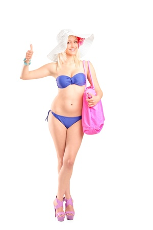 Full length portrait of an attractive blond woman in bikini giving a thumb up isolated on white background photo