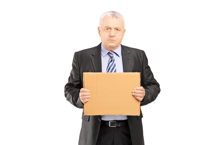 devastated: Sad middle aged businessman holding a piece of cardboard and looking at camera, isolated on white background