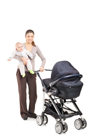 babysitter: Full length portrait of a young mother with a baby and a pushchair, isolated on white background