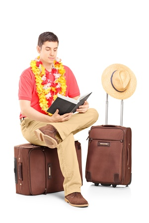 Male tourist sitting on a briefcase and reading a book, isolated on white background photo