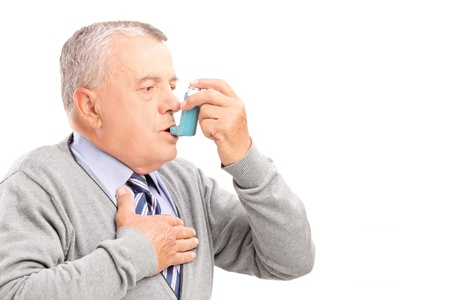 inhaler: Mature man taking asthma treatment, isolated on white background