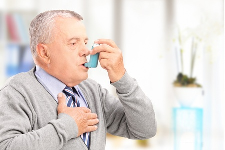 treating: Mature man treating asthma with inhaler at home