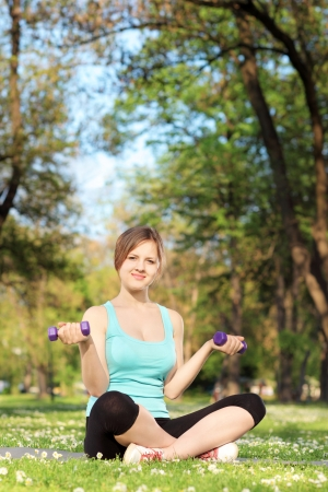 Young female exercising with dumbbells in a park Stock Photo - 19627661