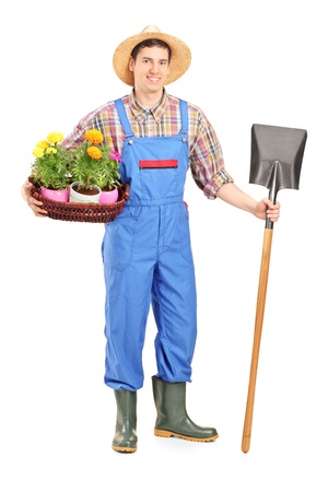horticulturist: Full length portrait of a male agricultural worker holding a shovel and flowers isolated on white background Stock Photo