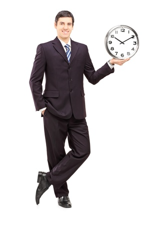 Full length portrait of a young man in suit holding a clock isolated on white background photo