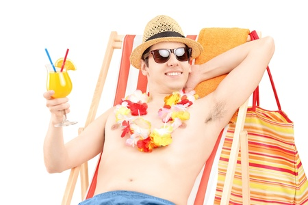 Happy young male sitting on a beach chair and drinking cocktail isolated on white background photo