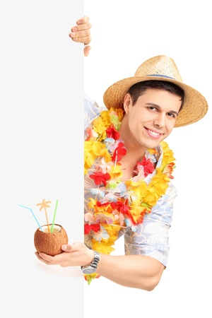 Smiling man in traditional costume behind a blank panel holding a coconut cocktail isolated on white background photo