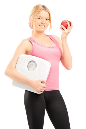Young smiling female holding a weight scale and a red apple isolated on white background photo