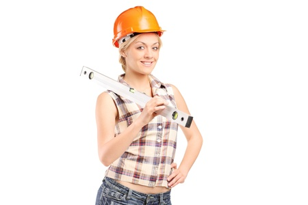 Smiling female worker with helmet holding a construction bubble level isolated on white background photo