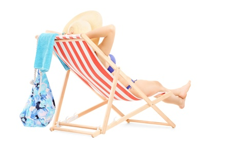 Young female in bikini lying on a beach chair isolated on white background photo