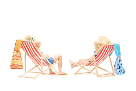 loungers: Couple relaxing on a sun loungers, isolated on white background Stock Photo