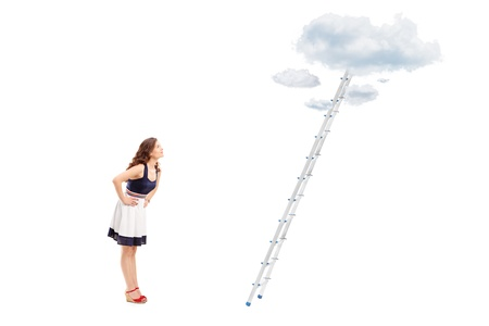 reachability: Full length portrait of a young woman standing in front of a ladder with cloud and looking, isolated on white background