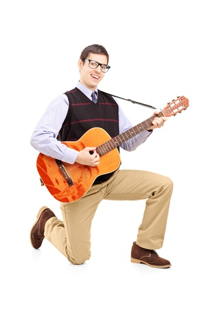 Young man playing an acoustic guitar and kneeling, isolated on white background Stock Photo - 19794700