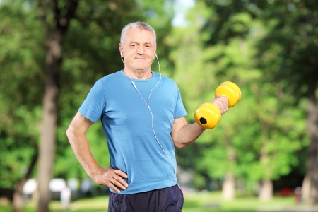 Mature man exercising with weight in a park photo