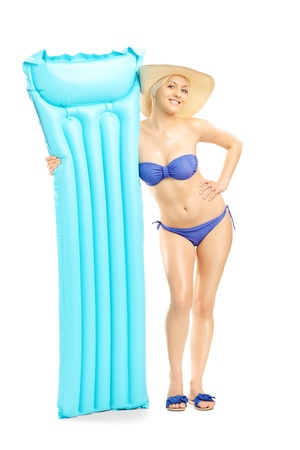 Full length portrait of a young woman in bikini holding a swimming mattress, isolated on white background photo
